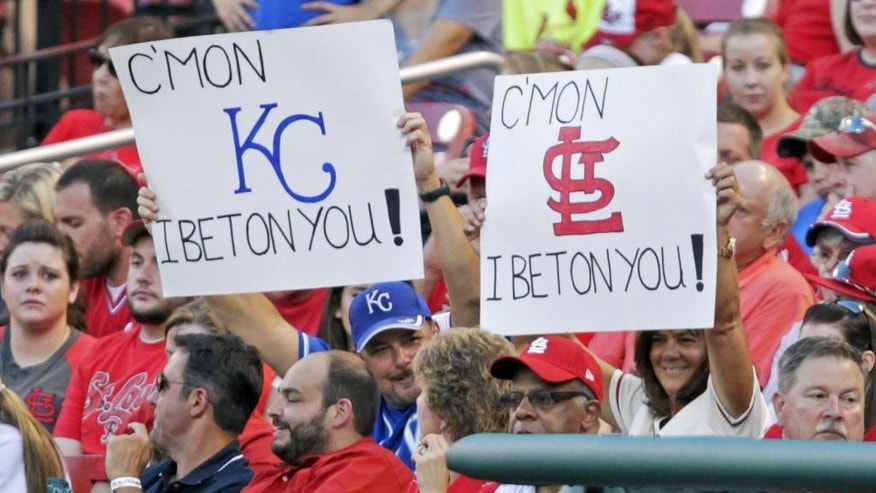 Two fans hold up signs for their respective teams in the first inning of a baseball game between the St. Louis Cardinals and the Kansas City Royals, Monday, June 2, 2014, in St. Louis.(AP Photo/Tom Gannam)