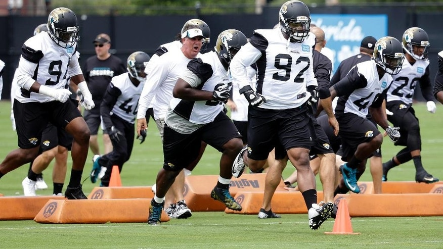 Members of the Jacksonville Jaguars defensive unit including defensive end Ziggy Hood (92) runs through drill during an NFL organized team activities football practice in  in Jacksonville, Fla., Monday, June 2, 2014. (AP Photo/John Raoux)
