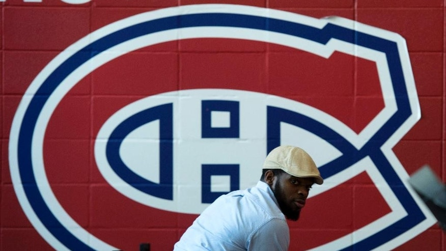Montreal Canadiens' P.K. Subban looks back as he signs souvenirs at the team's training facility Saturday, May 31, 2014 in Brossard, Quebec. The Canadiens were eliminated from the NHL hockey Stanley Cup playoffs by the New York Rangers in Game 6 of the Eastern Conference final on Thursday, May 29. (AP Photo/The Canadian Press, Paul Chiasson)