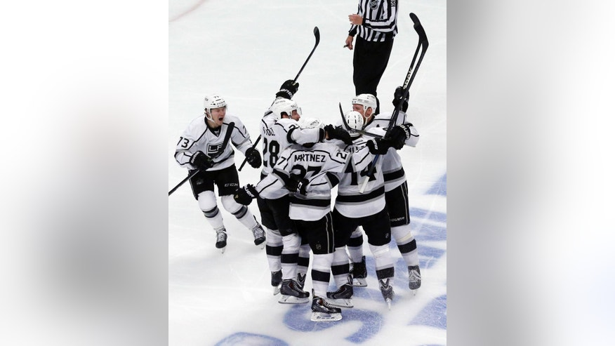 Los Angeles Kings defenseman Alec Martinez (27) celebrates the game winning goal with his teammates during the overtime period in Game 7 of the Western Conference finals in the NHL hockey Stanley Cup playoffs Sunday, June 1, 2014, in Chicago. The Kings won 5-4 in the overtime. (AP Photo/Charles Rex Arbogast)