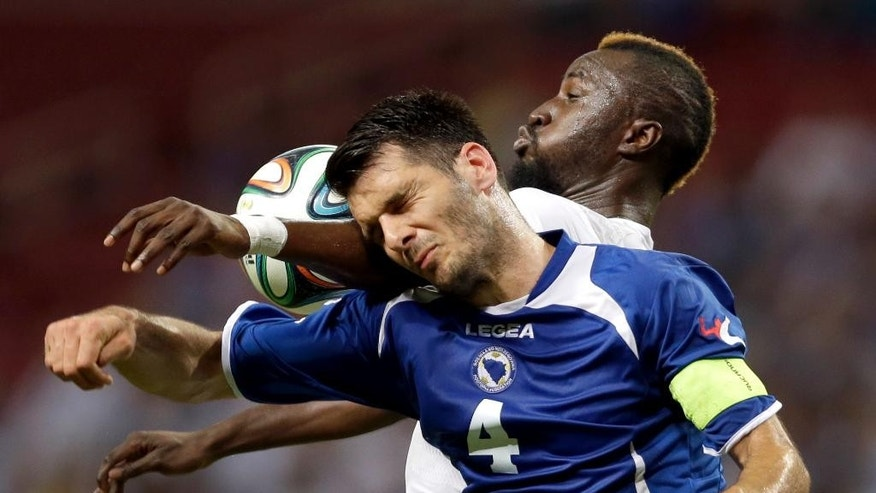 Bosnia-Herzegovina's Emir Spahic, front, and Ivory Coast's Lacina Traore vie for the ball during the first half in an international friendly soccer match Friday, May 30, 2014, in St. Louis. (AP Photo/Jeff Roberson)