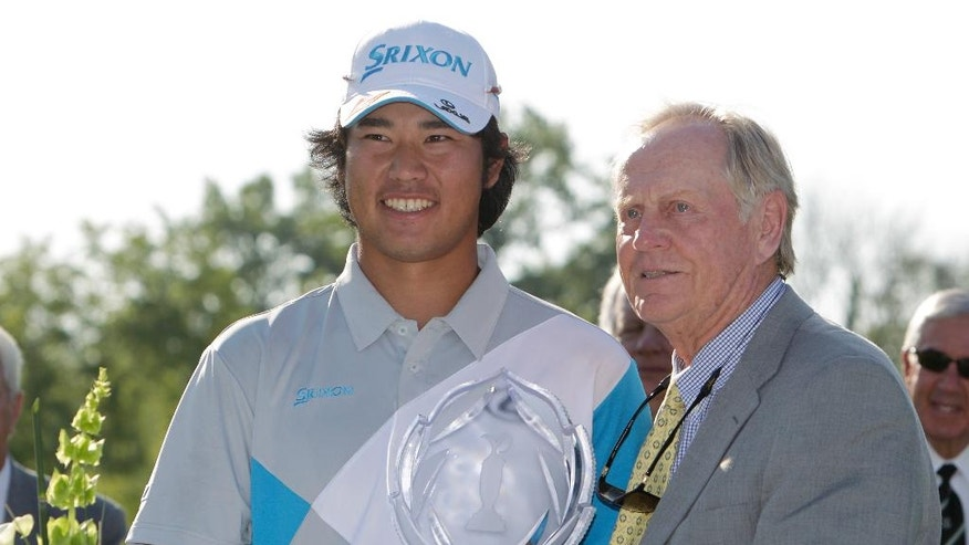 Jack Nicklaus, right, presents Hideki Matsuyama, of Japan, with the trophy after Matsuyama won the Memorial golf tournament on the first playoff hole Sunday, June 1, 2014, in Dublin, Ohio. (AP Photo/Jay LaPrete)