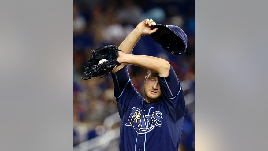 Tampa Bay Rays' Alex Cobb wipes his face after Miami Marlins' Marcell Ozuna double in the first inning of an interleague  baseball game in Miami, Monday, June 2, 2014. (AP Photo/Alan Diaz)