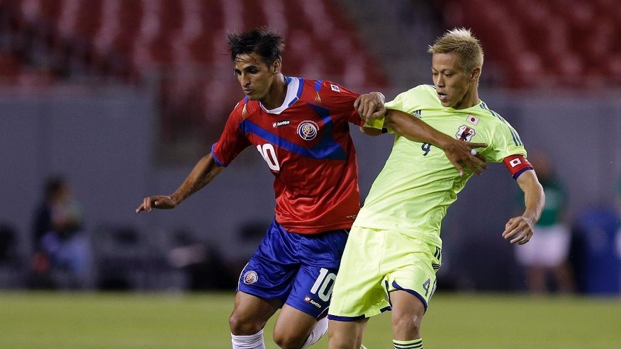 Costa Rica forward Bryan Ruiz (19) battles with Japan forward Keisuke Honda (4) for the ball during the first half of a friendly soccer match Monday, June 2, 2014, in Tampa, Fla. (AP Photo/Chris O'Meara)