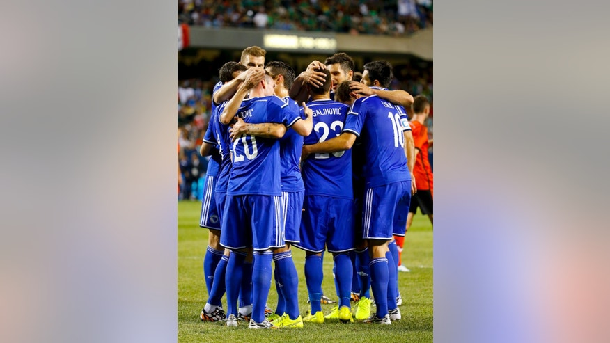 Bosnia-Herzegovina forward Izet Hajrovic (20) is congratulated by teammates after scoring against Mexico during the first half of an international friendly soccer match at Soldier Field in Chicago, Tuesday, June 3, 2014. (AP Photo/Kamil Krzaczynski)