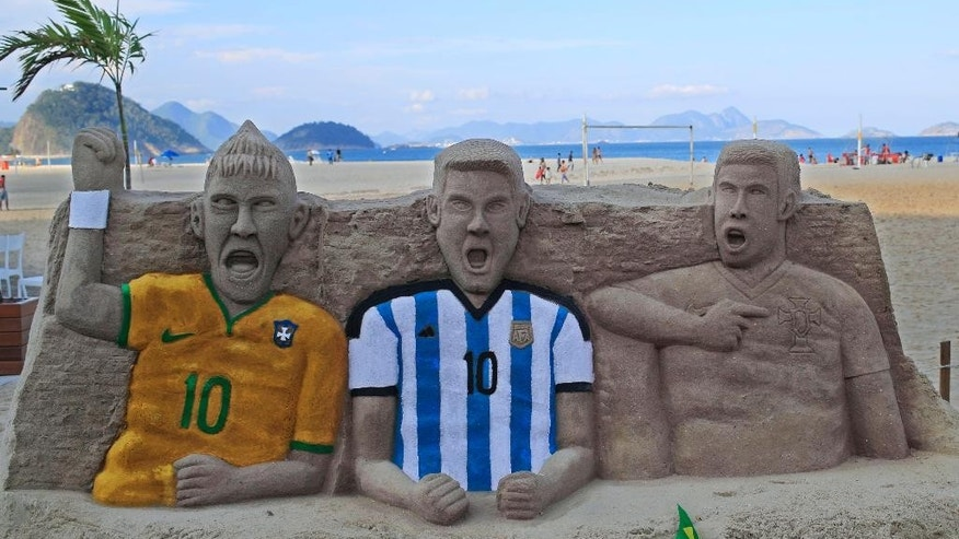 A sand sculpture featuring soccer players, from left to right, Neymar of Brazil, Lionel Messi of Argentina and Cristiano Ronaldo of Portugal, on Copacabana beach in Rio de Janeiro, Brazil, Monday, June 2, 2014. The 2014 Brazil World Cup is set to begin in a few days, with Brazil and Croatia competing in the opening match on June 12. (AP Photo/Hassan Ammar)