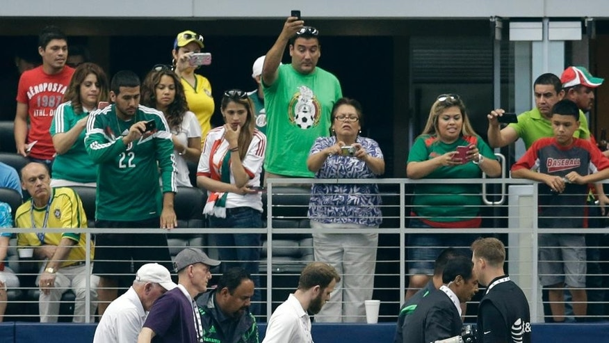 Fans look on as others make pictures while medical staff carry Mexico's Luis Montes on a stretcher off the field in the first half of a friendly soccer match against Ecuador, Saturday, May 31, 2014, in Arlington, Texas. Montes suffered an unknown leg injury during a collision with Ecuador's Segundo Castillo. (AP Photo/Tony Gutierrez)