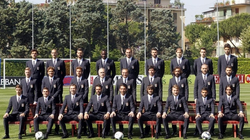 ADDS THE NAMES OF THE PLAYERS AND  OFFICIALS  Italian national soccer team pose with the official team suits, at the Coverciano center, near Florence, Italy, Tuesday, June 3, 2014. Front row, from left, sitting, Mattia De Sciglio, Marco Verratti, Antonio Cassano, Salvatore Sirigu, Gianluigi Buffon, Mattia Perin, Ciro Immobile, Lorenzo Insigne and Alberto Aquilani. Center row, from left, Ignazio Abate, Alessio Cerci, Claudio Marchisio, president of the Italian soccer federation Giancarlo Abete, coach Cesare Prandelli, vice-president of the Italian Soccer Federation Demetrio Albertini, Andrea Pirlo, Daniele De Rossi and Antonio Candreva. Third row, from left, Marco Parolo, Leonardo Bonucci, Thiago Motta, Mario Balotelli, Giorgio Chiellini, Andrea Barzagli, Gabriel Paletta, Matteo Darmian and Andrea Ranocchia. (AP Photo/Fabrizio Giovannozzi)