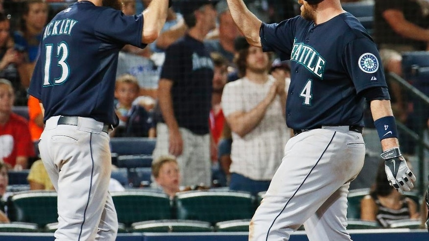 Seattle Mariners' John Buck (4) celebrates with Dustin Ackley (13) as he scores after hitting a two-run home run in the seventh inning of a baseball game against the Atlanta Braves on Tuesday, June 3, 2014, in Atlanta.  (AP Photo/John Bazemore)