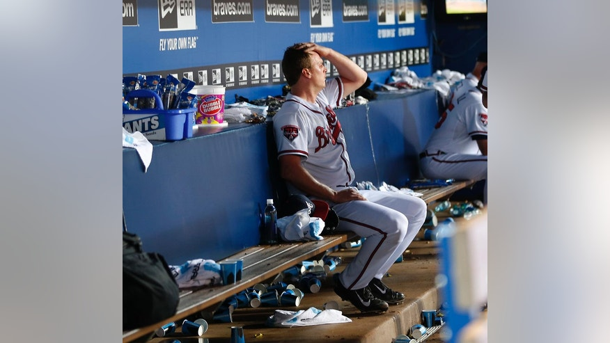 Atlanta Braves starting pitcher Gavin Floyd sits on the bench after being removed during the sixth inning of a baseball game against the Seattle Mariners on Tuesday, June 3, 2014, in Atlanta. (AP Photo/John Bazemore)