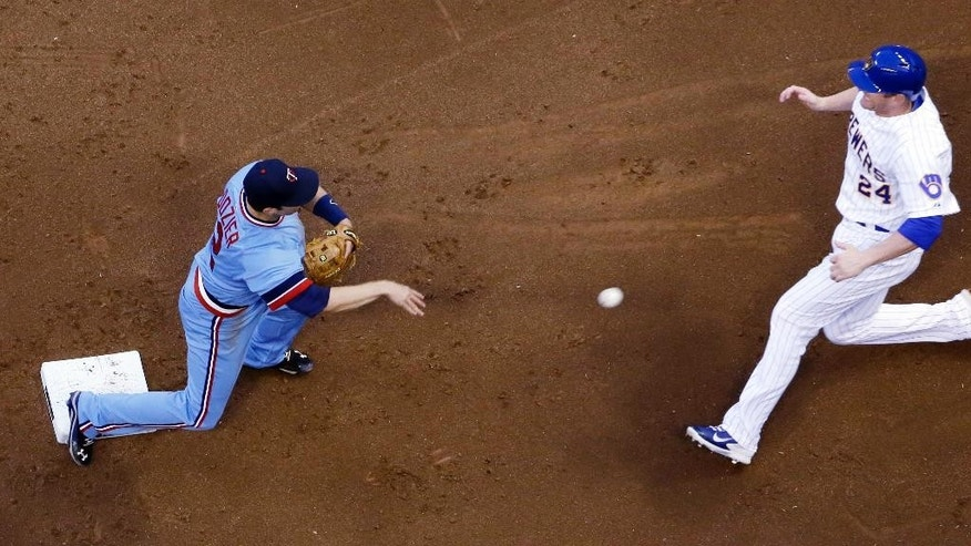 Milwaukee Brewers' Lyle Overbay (24) is out at second as Minnesota Twins' Brian Dozier turns a double play on a ball hit by Martin Maldonado during the second inning of a baseball game Tuesday, June 3, 2014, in Milwaukee. (AP Photo/Morry Gash)