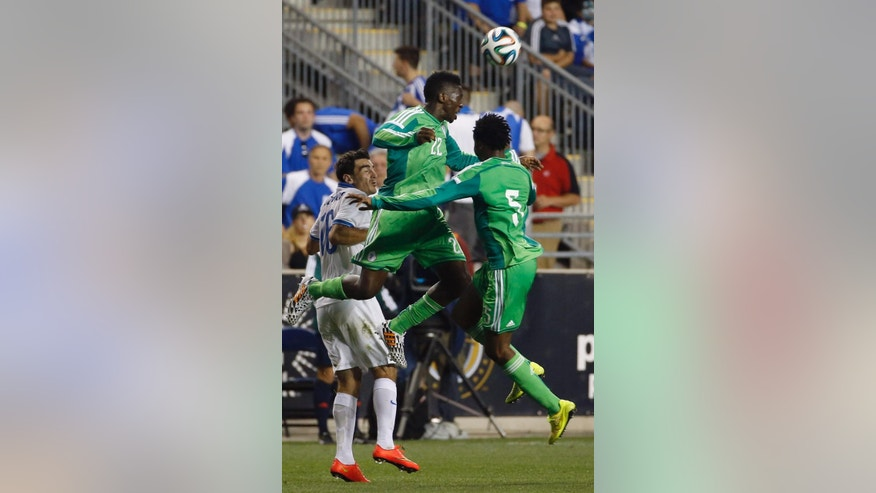Nigeria defenders Kenneth Omeruo (22) and Efe Ambrose (5) leaps for a header against Greece midfielder Lazaros Christodoulopoulos (16) during the second half of an international friendly soccer match, Tuesday, June 3, 2014, in Chester, Pa. The match ended in a tie, 0-0. (AP Photo/Matt Slocum)