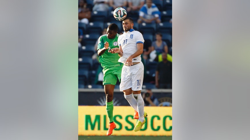 Greece defender Loukas Vyntra, right, and Nigeria defender Elderson Echiéjilé leap for a header during the first half of an an international friendly soccer match, Tuesday, June 3, 2014, in Chester, Pa. (AP Photo/Matt Slocum)