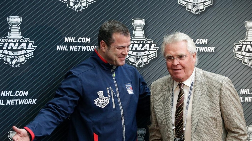 New York Rangers head coach Alain Vigneault, left, shows the way to the team's president and general manager Glen Sather after a news conference on Tuesday, June 3, 2014, in Los Angeles. The New York Rangers plays the Los Angeles Kings for in Game 1 of NHL Stanley Cup Final hockey series Wednesday. (AP Photo/Jae C. Hong)