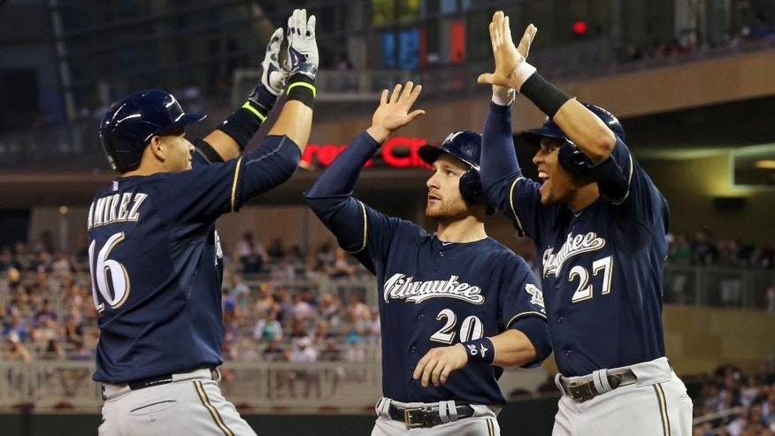 Milwaukee Brewers' Carlos Gomez, right, and Jonathan Lucroy, center, celebrate with Aramis Ramirez, left, after Ramirez hit a game-tying, three-run home run off Minnesota Twins  pitcher Ricky Nolasco in the seventh inning of a baseball game, Wednesday, June 4, 2014, in Minneapolis. (AP Photo/Jim Mone)