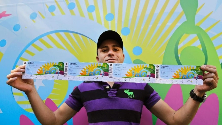 Colombia soccer fan John Gomes shows his newly bought tickets for Colombia's World Cup soccer games outside a ticket center at Ibirapuera Gym in Sao Paulo, Brazil, Wednesday, June 4, 2014. Tickets for the World Cup opener were sold out fast, as fans lined up in the cold to try to buy what was left for the other matches. (AP Photo/Nelson Antoine)