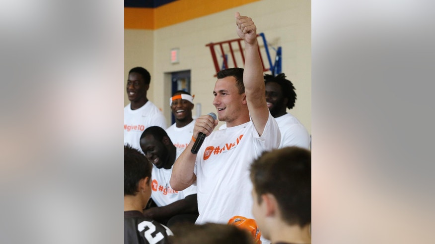 Cleveland Browns rookie quarterback Johnny Manziel gives a thumbs up after talking with students at Grindstone Elementary school in Berea, Ohio Wednesday, June 4, 2014. (AP Photo/Mark Duncan)