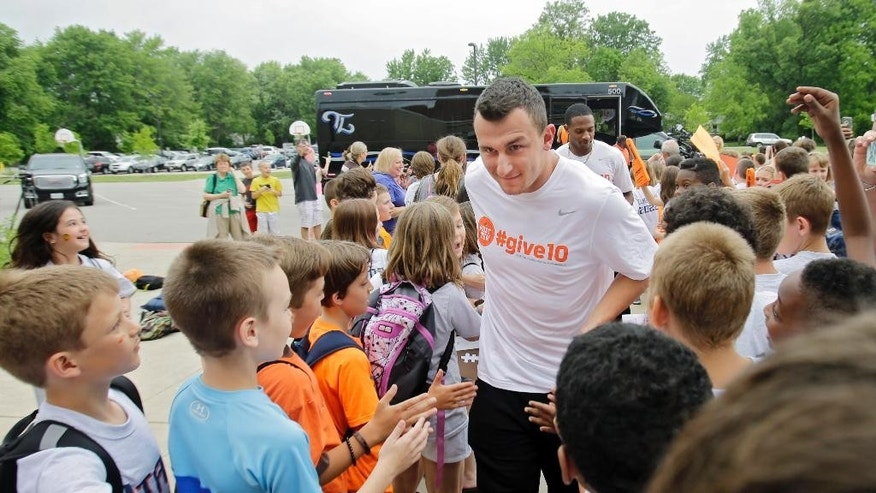 Cleveland Browns quarterback Johnny Manziel is greeted by students as he and the other Browns' rookies arrive at Grindstone Elementary school in Berea, Ohio for a community event Wednesday, June 4, 2014. (AP Photo/Mark Duncan)