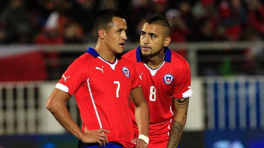 Chile's, Arturo Vidal, right and Alexis Sanchez, talk during an international friendly soccer against Northern Ireland, in Valparaiso, Chile, Wednesday, Jun 4, 2014. (AP Photo/Luis Hidalgo)