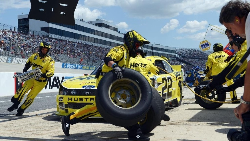 Joey Logano's pit crew works on his car during a pit stop during the the NASCAR Nationwide series auto race, Saturday, May 31, 2014, at Dover International Speedway in Dover, Del. (AP Photo/Molly Riley)