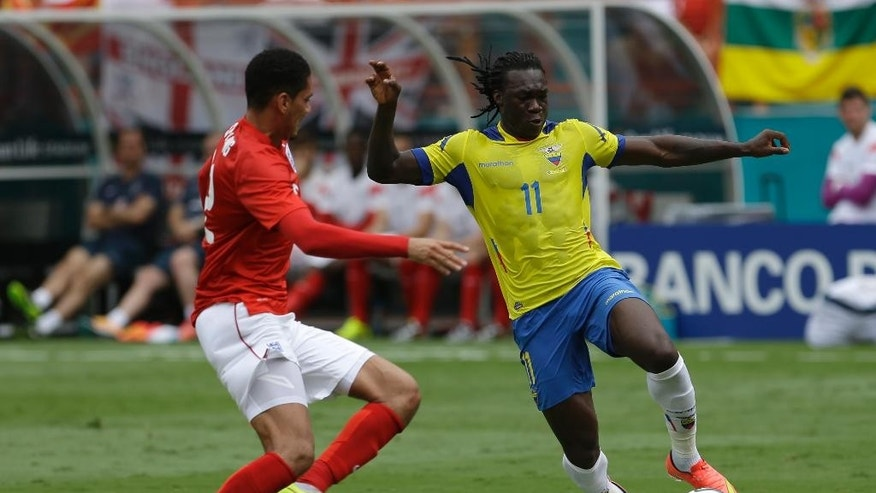 Ecuador's Felipe Caicedo (11) drives against England's Adrian Bone in the first half of a friendly soccer match in Miami Gardens, Fla., Wednesday, June 4, 2014. (AP Photo/Alan Diaz)