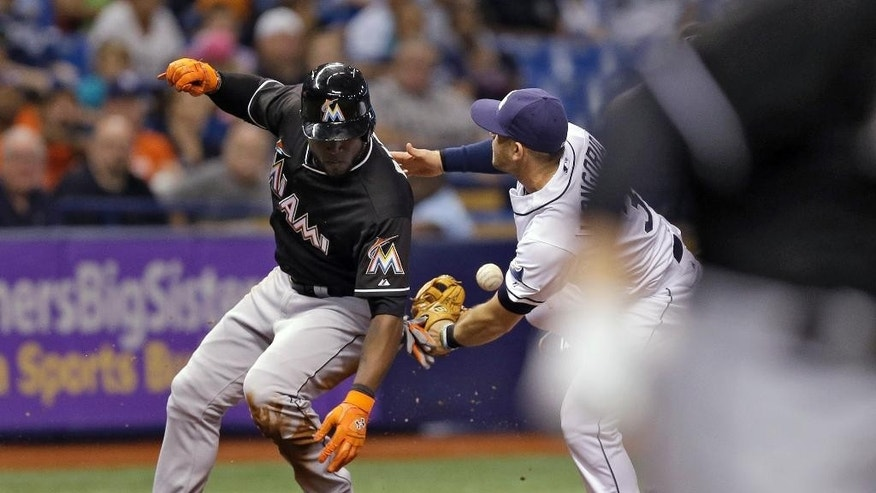 Miami Marlins' Marcell Ozuna is safe at third base after Tampa Bay Rays' Evan Longoria, right, dropped the ball attempting to tag him out during the third inning of an interleague baseball game Wednesday, June 4, 2014, in St. Petersburg, Fla. Marlins' Jeff Baker reached base on a fielder's choice. (AP Photo/Chris O'Meara)