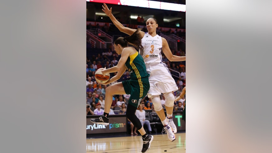 Seattle Storm's Sue Bird, left, passes the ball off as Phoenix Mercury's Diana Taurasi (3) defends during the first half of a WNBA basketball game on Tuesday, June 3, 2014, in Phoenix. (AP Photo/Ross D. Franklin)