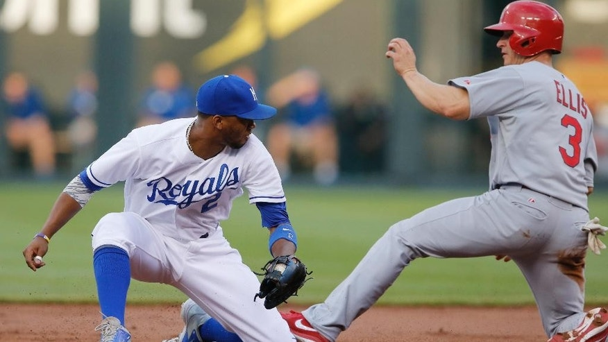St. Louis Cardinals' Mark Ellis (3) beats the tag by Kansas City Royals shortstop Alcides Escobar (2) during the second inning of a baseball game at Kauffman Stadium in Kansas City, Mo., Wednesday, June 4, 2014. Ellis was safe with a stolen base. (AP Photo/Orlin Wagner)
