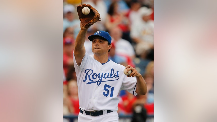 Kansas City Royals starting pitcher Jason Vargas changes balls after loading the bases during the first inning of a baseball game against the St. Louis Cardinals at Kauffman Stadium in Kansas City, Mo., Wednesday, June 4, 2014. (AP Photo/Orlin Wagner)