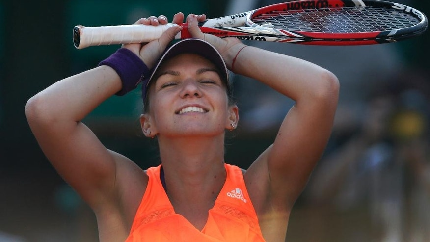 Romania's Simona Halep celebrates winning the semifinal match of the French Open tennis tournament against Germany's Andrea Petkovic at the Roland Garros stadium, in Paris, France, Thursday, June 5, 2014. Halep won in two sets 6-2, 7-6. (AP Photo/Darko Vojinovic)