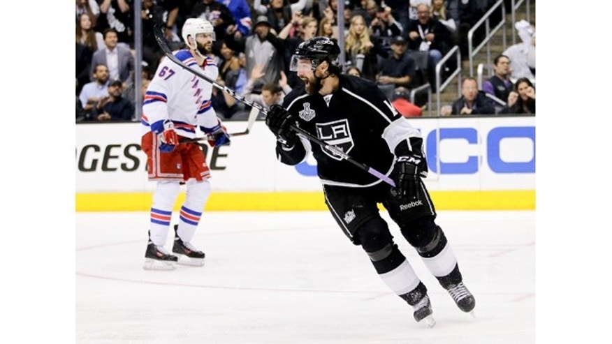 June 4, 2014: Los Angeles Kings right winger Justin Williams, right, celebrates his game winning goal as New York Rangers left wing Benoit Pouliot looks on in overtime of Game 1 in the NHL Stanley Cup Final in Los Angeles.(AP Photo/Jae C. Hong)