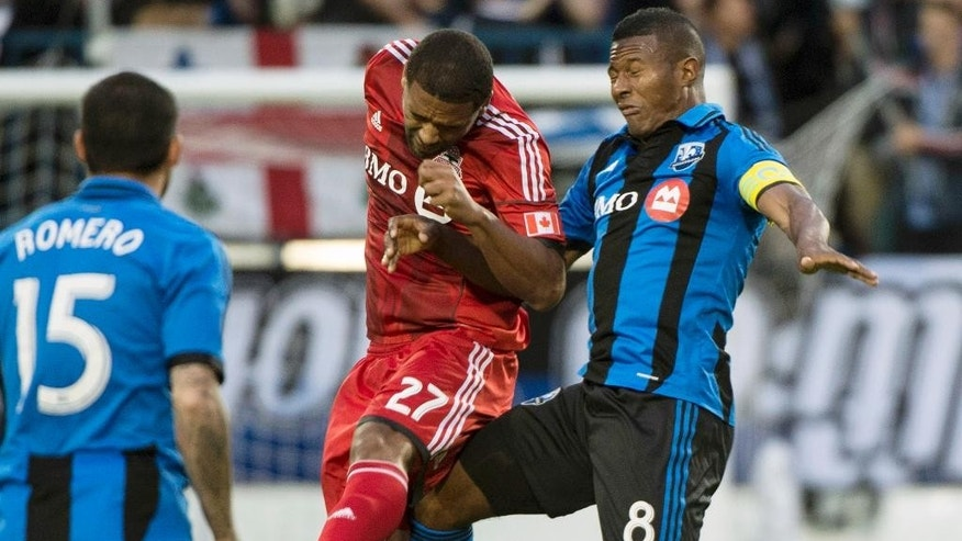 Toronto FC's Luke Moore heads the ball away from Montreal Impact's Patrice Bernier during the first half of the Voyageurs Cup, Wednesday, June 4, 2014 in Montreal. (AP Photo/The Canadian Press, Paul Chiasson)