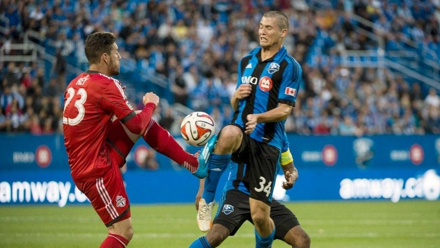 Toronto FC's Alvaro Rey kicks the ball away from Montreal Impact's Karl W. Ouimette during the first half of the Voyageurs Cup, Wednesday, June 4, 2014 in Montreal. (AP Photo/The Canadian Press, Paul Chiasson)