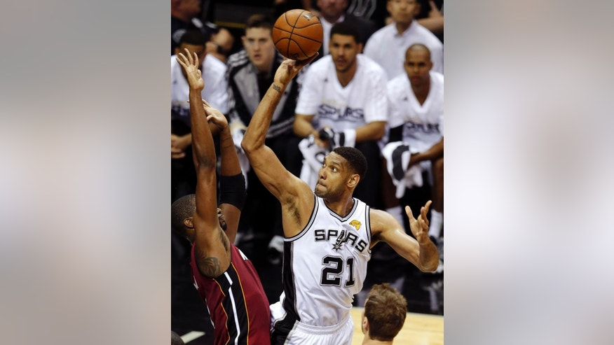San Antonio Spurs forward Tim Duncan (21) shoots over Miami Heat center Chris Bosh (1) during the first half in Game 1 of the NBA basketball finals on Thursday, June 5, 2014, in San Antonio. (AP Photo/Tony Gutierrez)