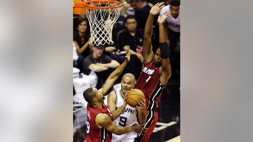 San Antonio Spurs guard Tony Parker (9) is defended by Miami Heat forward Rashard Lewis (9) and center Chris Bosh (1) during the first half in Game 1 of the NBA basketball finals on Thursday, June 5, 2014, in San Antonio. (AP Photo/Tony Gutierrez)