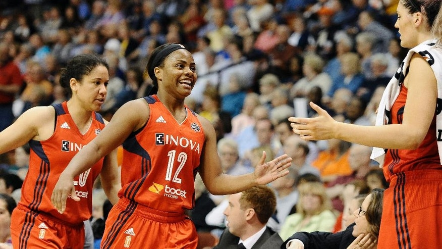 Washington Mystics' Ivory Latta, center, and teammate Kara Lawson, left, are greeted on bench by Stefanie Dolson during the second half of a WNBA basketball game against the Connecticut Sun, Thursday, June 5, 2014, in Uncasville, Conn. The Mystics defeated the Sun 74-66. (AP Photo/Jessica Hill)