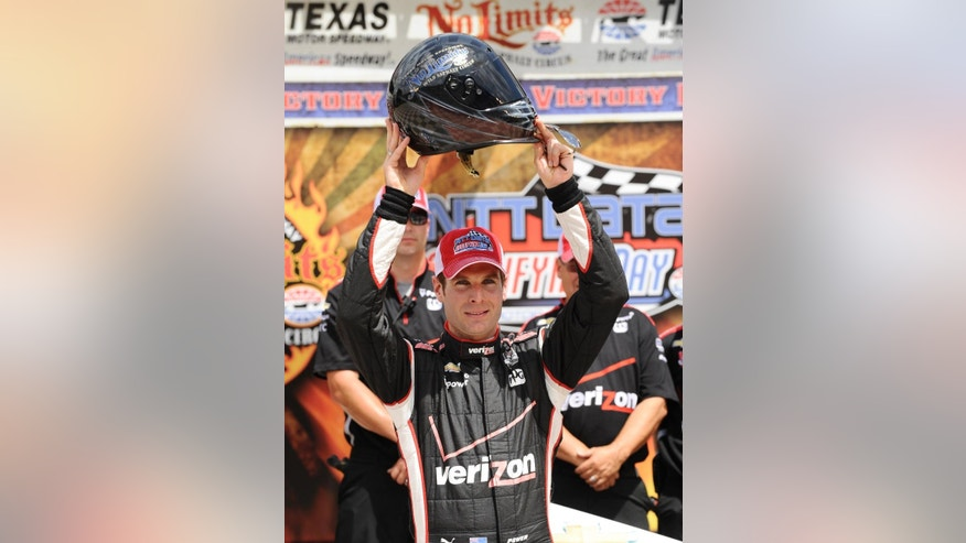 Will Power, of Australia, holds up the pole position helmet after posting the highest speed to take the pole position during qualifying for the IndyCar auto race at Texas Motor Speedway in Fort Worth, Friday, June 6, 2014. (AP Photo/Tim Sharp)