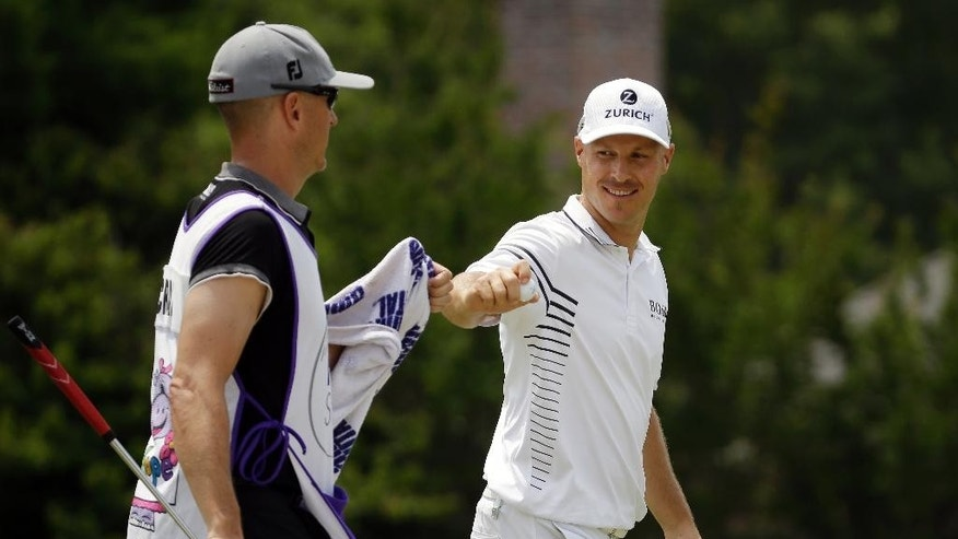 Ben Crane is congratulated by his caddie, left, after Crane sank a birdie putt on the 16th hole during the second round of the St. Jude Classic golf tournament Friday, June 6, 2014, in Memphis, Tenn. (AP Photo/Mark Humphrey)