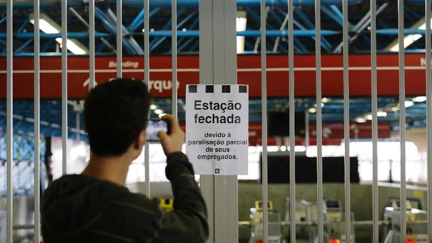 "A commuter takes a photo of a sign that reads in Portuguese ""Station closed"" at the Arthur Alvim metro station in Sao Paulo, Brazil, Thursday, June 5, 2014. This city that will host the World Cup opening match in a week was thrown into transit chaos Thursday as subway and overland commuter train operators went on strike, putting at risk the only means that most soccer fans will have to reach the stadium. (AP Photo/Nelson Antoine)"