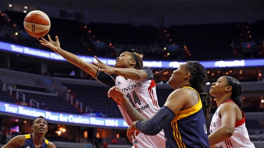 Washington Mystics guard Tierra Ruffin-Pratt (14) shoots between Indiana Fever forwards Natasha Howard (33) and Erlana Larkins (2) during the first half of a WNBA basketball game Friday, June 6, 2014 in Washington.  (AP Photo/Alex Brandon)