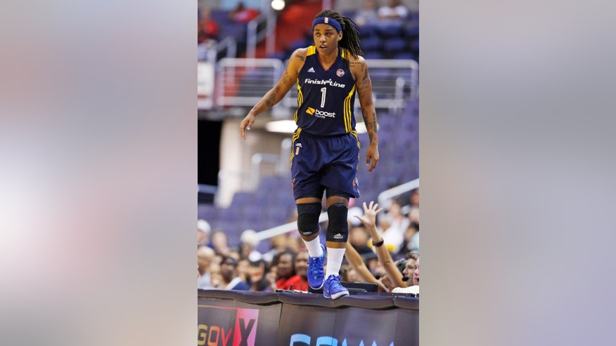 Indiana Fever guard Shavonte Zellous (1) walks on the edge of the scorer's table after jumping up there after a loose ball during the first half of a WNBA basketball game against the Washington Mystics Friday, June 6, 2014 in Washington.  (AP Photo/Alex Brandon)