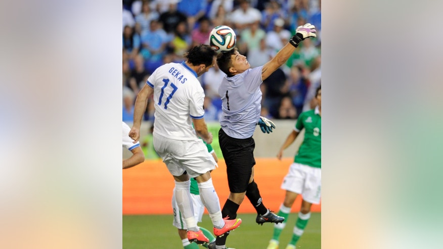 Bolivia goalkeeper Romel Javier Quinonez goes up for a save as Greece's Thoefanis Gekas attempts a header during the first half of an international friendly soccer match Friday, June 6, 2014, in Harrison, N.J.. (AP Photo/Bill Kostroun)