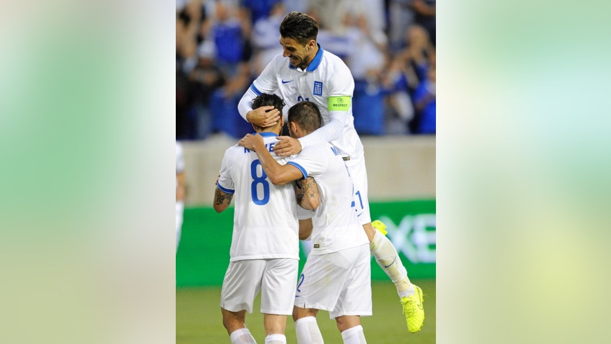 Greece's Kostantinos Katsouranis, top, and Ioannis Maniatis, right, celebrate with Guergki Panagiotis Kone (8) after Kone scored during the first half of an international friendly soccer match against Bolivia Friday, June 6, 2014, in Harrison, N.J.. (AP Photo/Bill Kostroun)