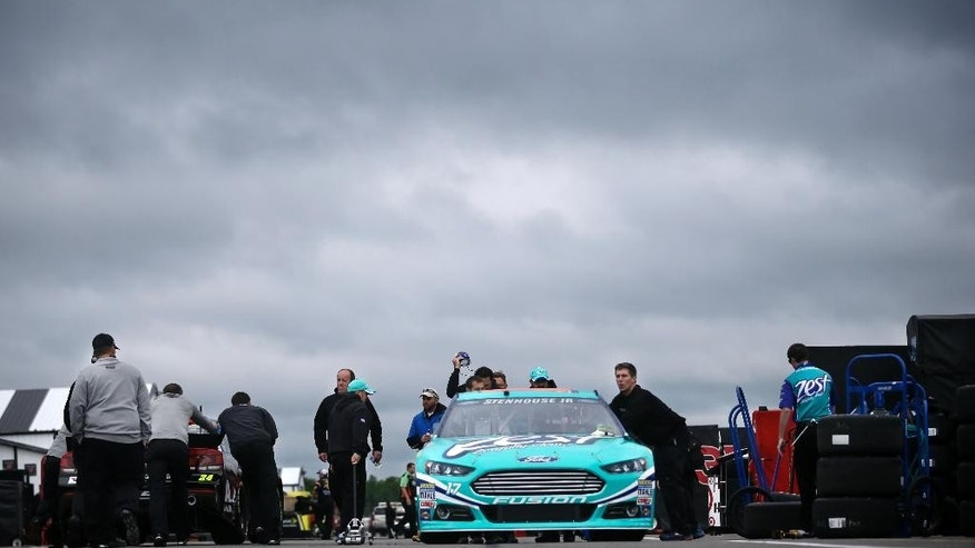 Crew members push the race car of Ricky Stenhouse Jr., under cloudy skies at Pocono Raceway before practice for Sunday's NASCAR Sprint Cup Series auto race in Long Pond, Pa., Friday, June 6, 2014. (AP Photo/Mel Evans)
