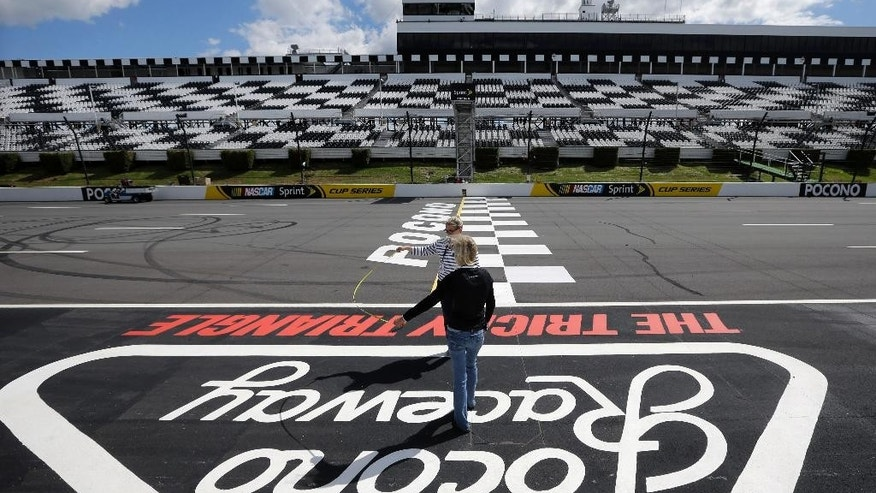 Two women measure the width of the front straight at the finish line at Pocono Raceway as preparations are made for Sunday's NASCAR Sprint Cup Series auto race in Long Pond, Pa., Thursday, June 5, 2014. (AP Photo/Mel Evans)