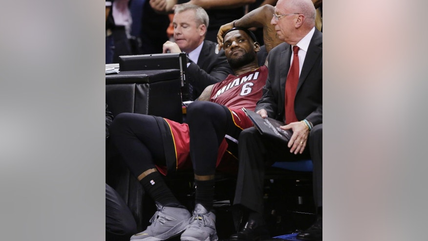 Miami Heat forward LeBron James (6) sits on the bench after injuring himself against the San Antonio Spurs during the second half in Game 1 of the NBA basketball finals on Thursday, June 5, 2014 in San Antonio. (AP Photo/Eric Gay)