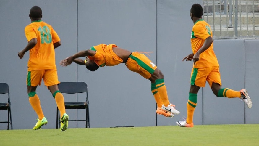Zambia's Christopher Katongo, center, does a back flip with teammates Emmanuel Mbola, left, and George Chilufya, right, after scoring a goal against Japan during the first half of an international friendly soccer match in Tampa, Fla., Friday, June 6, 2014. (AP Photo/John Raoux)
