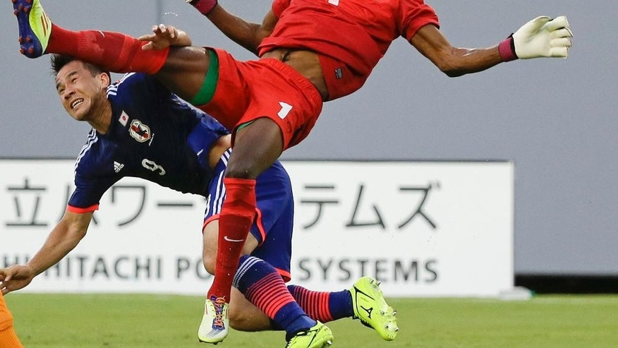 Japan's Shinji Okazaki (9) and Zambia goal keeper Toaster Nsabata (1) fall to the ground after a collision while going up for the ball during the first half of an international friendly soccer match in Tampa, Fla., Friday, June 6, 2014. Both players were injured but remained in the game.(AP Photo/John Raoux)