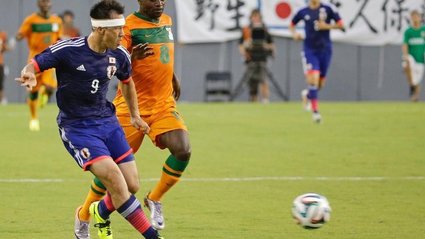 Japan's Shinji Okazaki (9) clears the ball away from Zambia's Isaac Chansa (8) during the first half of an international friendly soccer match in Tampa, Fla., Friday, June 6, 2014. (AP Photo/John Raoux)