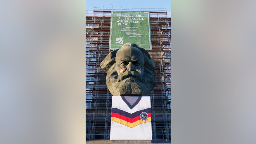 "In this picture taken Thursday June 5, 2014, the statue  of German philosopher , economist  Karl Marx is wrapped with a German national soccer shirt in Chemnitz, eastern Germany. The statue of the father of  communism now sports Germany flags on its cheeks. Authorities say they dressed up the 40-ton bronze head  - unveiled by communist East Germany in 1971 - to project a ""friendly"" image. However, they concede that the idea isn't universally popular. Marx's makeover hasn't gone entirely smoothly: an outsize Germany shirt draped over his pedestal was stolen in the early hours of  Friday and found damaged nearby a few hours later. (AP Photo/dpa, Harry Haertel)"